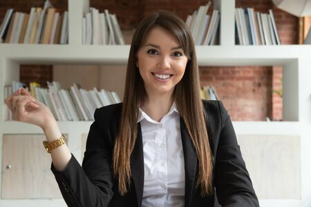 Headshot portrait of smiling Caucasian young businesswoman sit at office desk having webcam video call, confident happy millennial female employee look at camera, shooting tutorial or presentation
