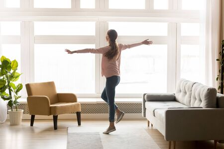 Happy active young woman dancing alone in modern living room interior with big window enjoying cozy weekend lifestyle, joyful carefree millennial girl listening music having fun at home apartment