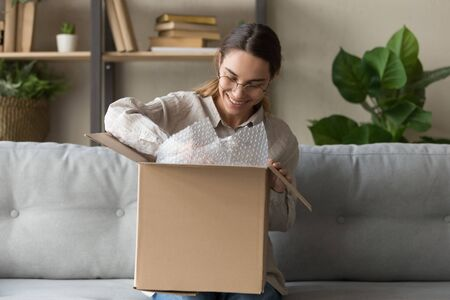 Smiling satisfied young woman customer sit on sofa unpack package open parcel, happy girl consumer holding cardboard box receive good online shop purchase at home, post mail shipping delivery concept Archivio Fotografico