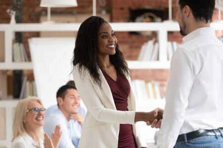 Male company ceo or boss shake hand of excited african American female employee congratulating with success or promotion, smiling multiracial colleagues shake hands greeting get acquainted at meeting Reklamní fotografie