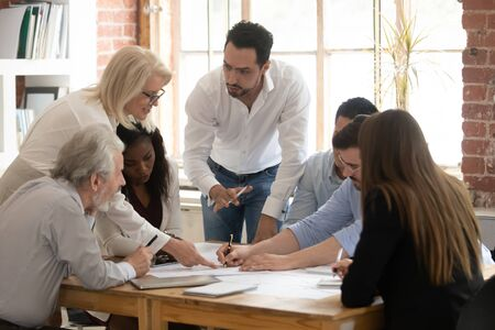 Multiracial diverse company employees brainstorm discussing business startup project sharing ideas at meeting, motivated colleagues talk consider paperwork plan financial stats cooperating at briefing