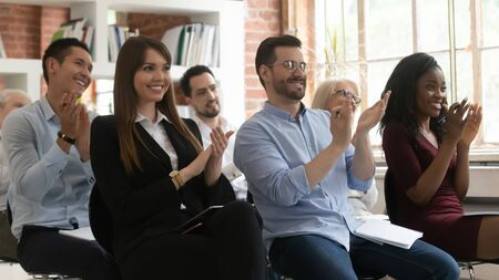 Excited multiracial office employees sit applaud thanking speaker for lecture or business seminar, happy overjoyed diverse workers or company interns clap hands greeting presenter or coach at meeting Фото со стока
