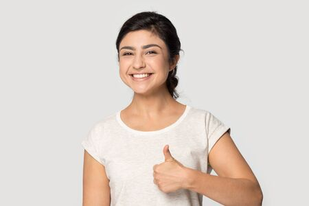 Portrait of happy young indian woman stand isolated on grey studio background look at camera recommend good service, smiling millennial ethnic girl posing show thumbs up give recommendation