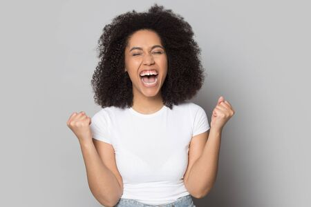 Overjoyed african American young curly woman isolate don grey studio background scream with happiness triumph, excited biracial millennial girl feel emotional euphoric with win, reward concept Stock fotó