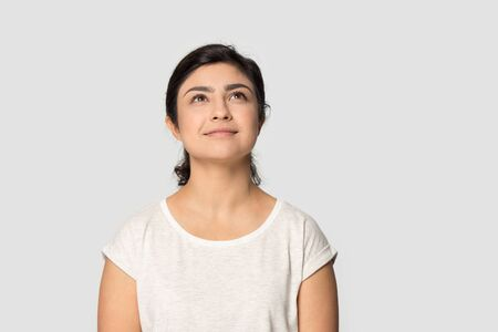 Dreamy happy young indian woman in casual t-shirt stand isolated on grey studio background look up thinking, thoughtful pensive ethnic millennial girl dreaming make wish, imagining or visualizing