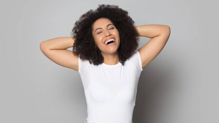 Happy african American millennial girl isolated on grey studio background stretching relaxing, smiling mixed race ethnicity young woman close eyes laugh enjoy positive moment, stress free concept Stockfoto