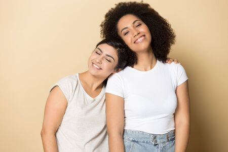 Happy millennial international girlfriends isolated on orange brown studio background hug posing together, smiling multiethnic young women friends look at camera embrace, friendship concept