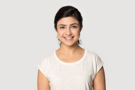 Headshot portrait of happy indian millennial girl stand isolated on grey studio background wear t-shirt look at camera, smiling ethnic young woman posing showing white healthy teeth, dental treatment Фото со стока