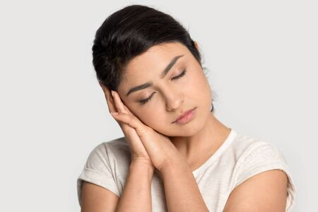 Tired indian millennial girl isolated on grey studio background hold head on hands fall asleep, exhausted ethnic young woman relax sleeping, feel fatigue or exhaustion, dreaming seeing good dreams