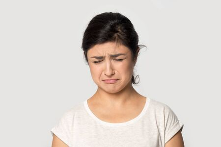 Unhappy indian millennial girl isolated on grey studio background feel down depressed suffer from life problems, sad gloomy ethnic young woman crying struggle with depression or breakup