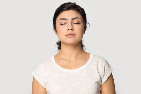 Peaceful millennial indian girl isolated on grey studio background relieve negative emotions breathe fresh air, calm young ethnic woman meditate with eyes closed, stress free, meditation concept Stockfoto