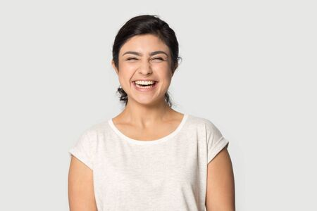 Excited indian young woman in casual weat t-shirt posing isolated on grey studio background laughing, headshot portrait of overjoyed ethnic millennial girl feel happy pleased, humor concept