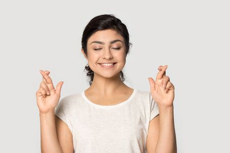 Une fille indienne du millénaire souriante, les yeux fermés, isolée sur fond gris studio, les doigts croisés font un vœu, une jeune femme ethnique superstitieuse se sent heureuse de croire en la chance, concept de superstition Banque d'images