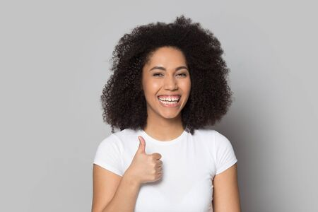 Smiling african American young woman isolated on grey studio background show thumbs up recommend good service, happy biracial millennial girl look at camera laughing give sincere recommendation