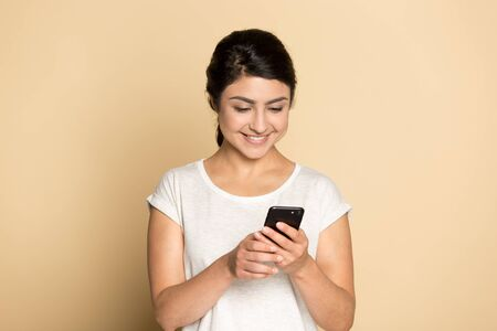 Smiling millennial indian girl isolated on orange brown studio background text message on cellphone, happy ethnic young woman using smartphone, have pleasant call, good wireless connection on cell