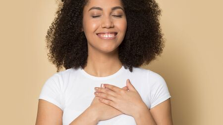 Close up of thankful african American millennial girl isolated on brown studio background hold hands at chest feel grateful, happy biracial young woman believer thank god, faith, superstition concept