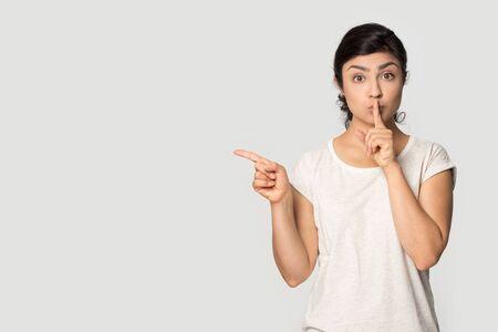 Millennial Indisch meisje in t-shirt geïsoleerd op grijze studio-achtergrond houd vinger op de lippen vraag wees stil, wijs op lege kopieerruimte opzij, toon goede verkoopdeal of kortingsaanbieding, geef geheime aanbeveling Stockfoto