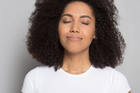 Close up of happy peaceful african American young woman isolated on grey studio background breathe fresh air, smiling calm biracial millennial girl relax relieve negative emotions, stress free concept