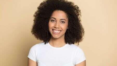 Headshot portrait of smiling african American millennial girl isolated on orange brown background look at camera, happy biracial young woman with curly hair wear white t-shirt posing in studio Stock Photo