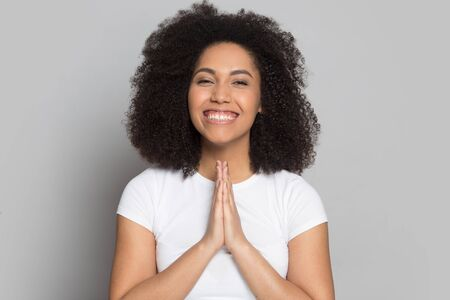 Smiling african American millennial girl with curly hair isolated on grey studio background look at camera laughing, happy biracial young woman hold hands in prayer feel thankful grateful for luck Stock fotó