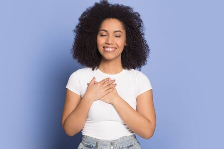 Happy mixed race ethnicity millennial girl isolated on blue studio background hold hands at heart chest feel grateful, african American thankful young woman believer show faith, superstition concept
