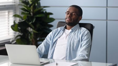 Distracted from job happy african american millennial worker reclining on chair, daydreaming at office. Mindful smart manager in eyeglasses relaxing, reducing stress, renewing energy at workplace.