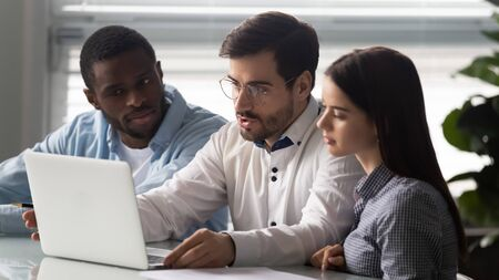 Serious successful team leader working together with mixed race colleagues. Focused diverse teammates listening too new project explanation. Concentrated manager reviewing working results on computer.