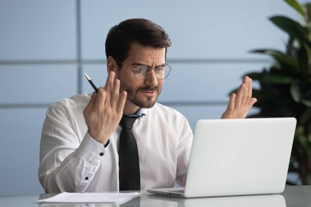Stressed young businessman looking at laptop screen, annoyed by bad news email head shot. Unhappy director dissatisfied with project results. Angry manager irritated by poor internet connection. Stockfoto