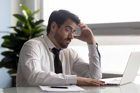 Concentrated millennial businessman thinking over problem solution. Tired young worker stuck with hard task at workplace. Pensive manager looking at computer screen, making difficult decision.