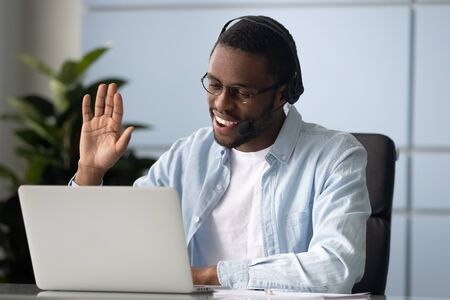 Head shot smiling african american entrepreneur wearing headphones, holding video call with clients, greeting partners at office. Intelligent mixed race speaker welcoming online webinar participants. Stock fotó - 131664698