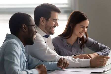 Side view overjoyed multiracial teammates sitting together at table, looking at laptop screen, watching funny video. Happy laughing young mixed race colleagues enjoying break time at workplace.