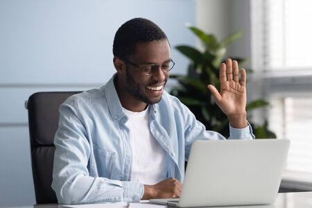 Happy african american worker in eyeglasses sitting at table with computer, holding video call with partners or clients. Confident mixed race speaker recording lecture, waving hello to subscribers.