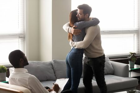 Young married couple standing near couch, hugging, reconciling after family problem solving at psychologist meeting. Loving spouse embracing cuddling, demonstrating peace, understanding, support.