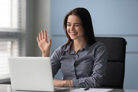 Happy young businesswoman holding video call with clients or greeting partners at workplace. Smiling millennial trainer speaker recording educational webinar lecture, waving hello to participants.