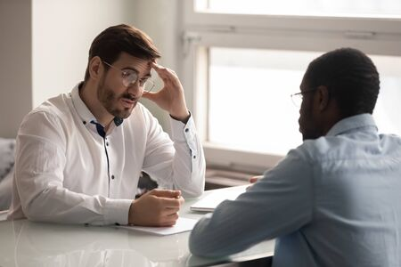 Confused unsure young hr manager in eyeglasses listening to flimsy african american job applicant. Millennial mixed race guy work candidate making bad first impression on recruiter at interview. Stockfoto