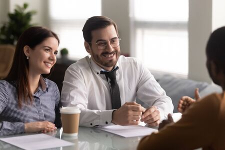 Head shot happy hr managers holding job interview with successful work candidate. Interested employers listening to interns self presentation. Recruitment, good first impression, employment concept.