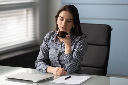 Young confident female manager worker entrepreneur using mobile voice recognition app, searching information in internet at workplace. Friendly businesswoman recording voice message on smartphone.