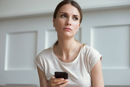 Pensive thoughtful young 30s woman holding smartphone look away lost on sad thoughts waiting first step from man, call or text message or date invitation from boyfriend feels jealousy and concerned