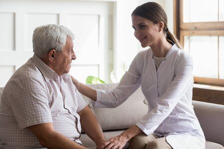Old man and careful nurse talk indoors, patient and caregiver seated on couch, medical specialty, good nurse feels compassion and provide comfort communication interpersonal skills and empathy concept Banco de Imagens - 131395016