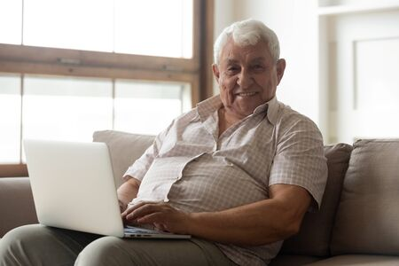 Healthy 80s old man seated on couch with laptop smiles looking at camera, enjoy time in internet, easy usage of medical apps for elderly patient online chat with doctor convenient program use concept