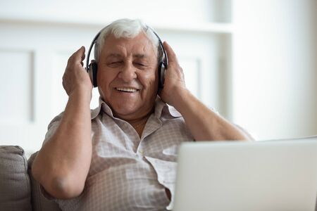 Senior man seated on sofa in living room hold laptop on lap wearing headphones listens favourite track having nostalgic mood enjoys songs of his youth, older generation using modern technology concept Banco de Imagens