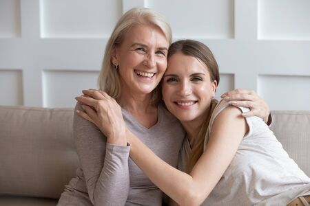 Beautiful elderly mother and adult daughter embracing holds hands smiling look at camera while resting on couch at home, caress and care, mom is best friend, always understand, always support concept