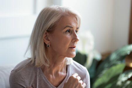 Gros plan, une femme âgée mélancolique des années 60 regarde au loin le visage éclairé par la lumière du soleil lorsqu'elle se sent blessée et seule, vieille femme pensive perdue dans des pensées tristes, processus de vieillissement, passe par le concept de problèmes personnels de divorce