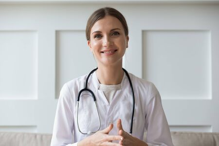 Head shot of woman wearing white coat stethoscope on shoulders looking at camera, doctor make video call interact through internet talk with patient provide help online counseling and therapy concept 版權商用圖片
