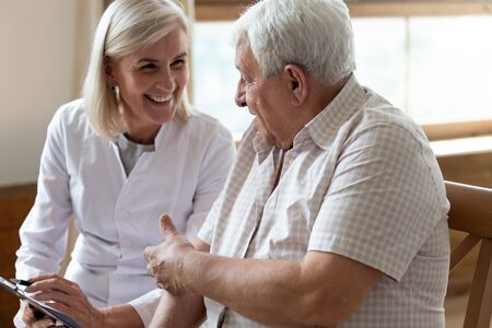 Älterer Patient der 80er Jahre und Krankenschwester mittleren Alters, der persönliche Informationen in der Zwischenablage schreibt und ein angenehmes, warmes Gespräch mit dem Pflegedienstkonzept des Klinikkunden führt