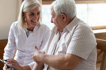Anziano uomo degli anni '80 paziente e infermiera di mezza età operatore medico in possesso di appunti che scrivono informazioni personali con una piacevole conversazione calda conversazione con il concetto di servizio di assistenza infermieristica del cliente della clinica