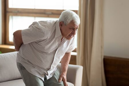 Senior grey haired 70s years man got up from couch writhes in pain felt sharp ache suffers from low back strain, touch loin reduce backache. Degenerative disk disease, pinched nerve rheumatism concept