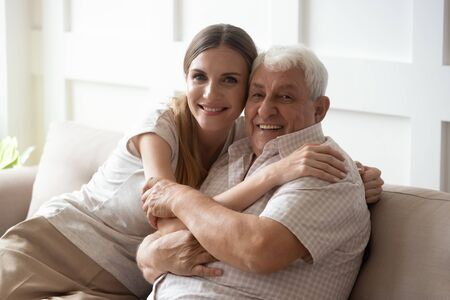Adult granddaughter and elderly 80s grandfather sitting together on couch posing look at camera, loving intergenerational family portrait warm love and care between people different generation concept