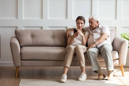 In living room on one side of sofa sitting old elderly 80s grandfather with adult 30s granddaughter, woman holding smartphone showing to older man new app, teach how use device help with usage concept