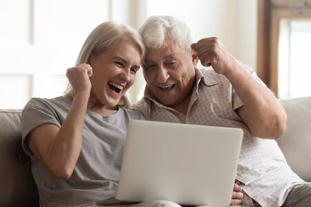 Elderly couple seated on couch looking at laptop screen scream with joy feels excited happy celebrating lottery victory, lucky moment, got online opportunity, sales and discounts e-commerce concept